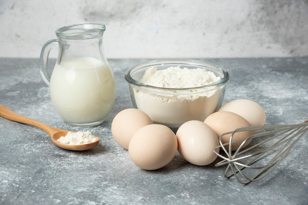Kom met bloem, eieren en melk op marmer. Gratis Foto