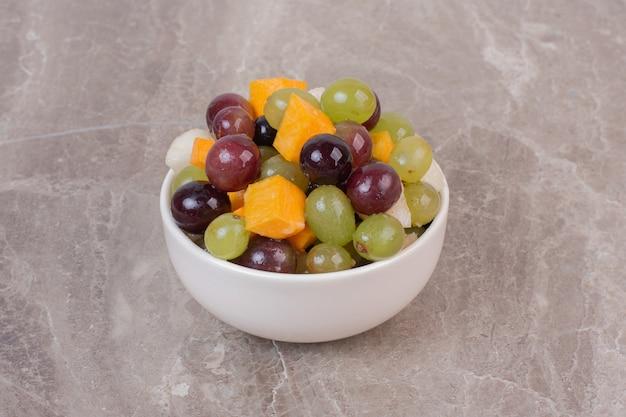 Kom met gemengd fruit op marmeren oppervlak. Gratis Foto