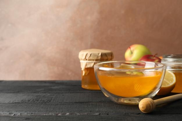 Kom met honing, beer en vruchten op houten achtergrond, ruimte voor tekst Premium Foto