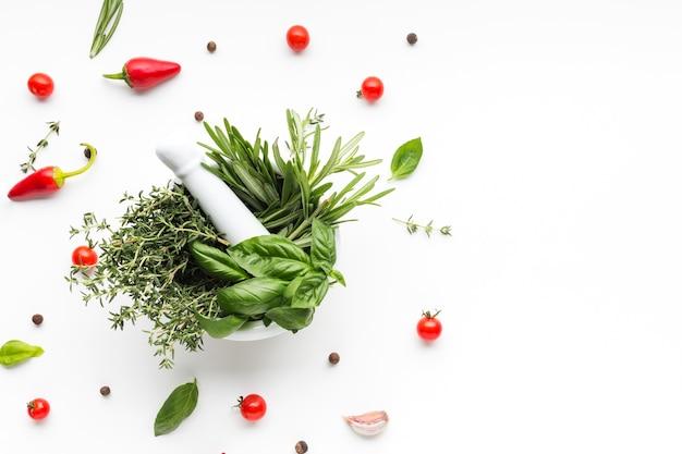 Kom met kruiden omringd door groenten Gratis Foto