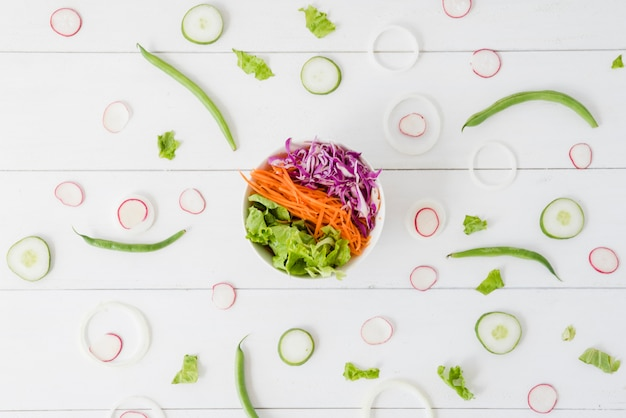 Kom met salade met raap; komkommer; ui plakjes met groene bonen op houten bureau Gratis Foto