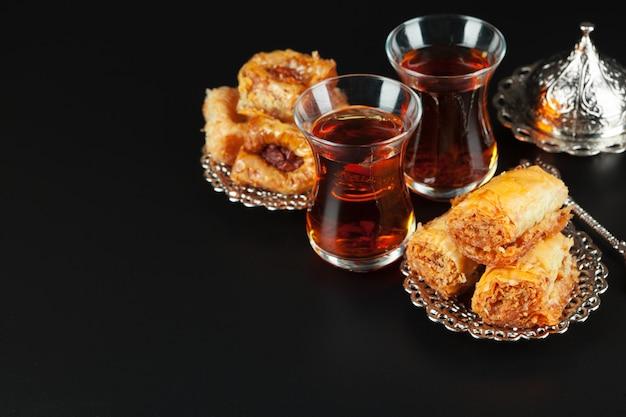Kom met stukjes turks fruitlokum en zwarte thee Premium Foto