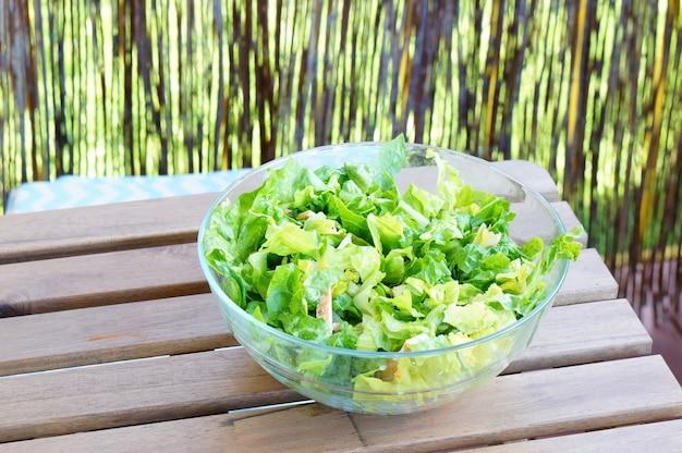 Kom met verse groene saladebladeren op een houten lijst Gratis Foto