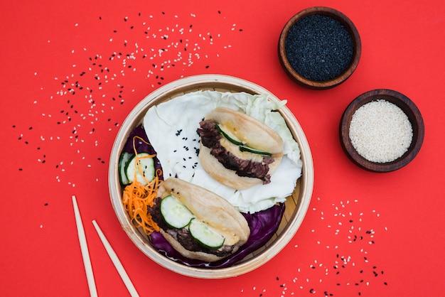 Kom met witte en zwarte sesamzaadjes met gua bao in stoomboot op rode achtergrond Gratis Foto