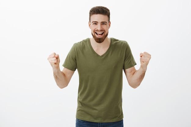 Kom op je kan het. actieve en opgewonden gelukkige knappe man met baard gebalde vuisten in gejuich, ondersteunende bemoedigende vriend, team scorendoel kijken, overwinning vieren, triomferen Gratis Foto
