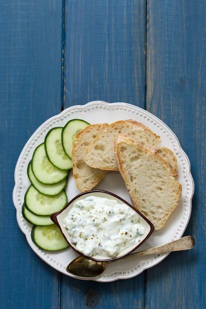 Komkommerdip met brood op plaat Premium Foto