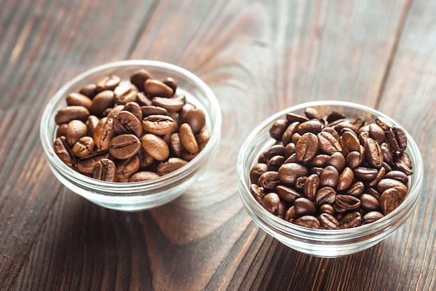 Kommen arabica en robusta koffiebonen Premium Foto