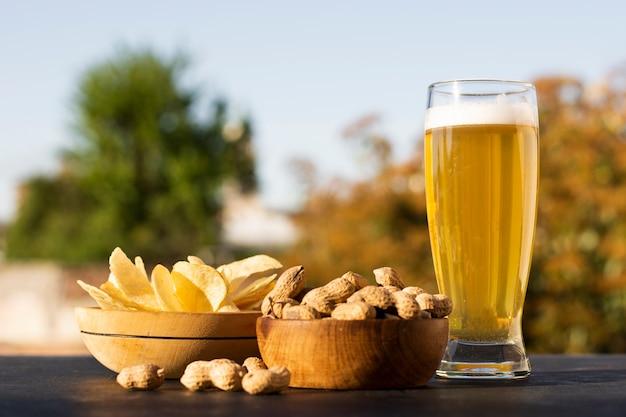 Kommen met chips en pinda's samen met bierglas Premium Foto
