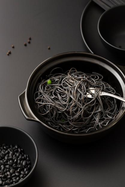 Kommen met donkere pasta en bonen op een donkere tafel Gratis Foto