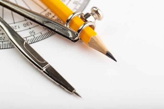 Kompas dichterbij bekijken met potlood voor tekenen en tekenen op witte muur Gratis Foto