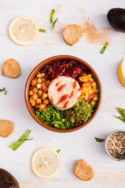 Komschotel met rijst en groenten die met citroen en brood op witte geweven achtergrond wordt omringd Gratis Foto