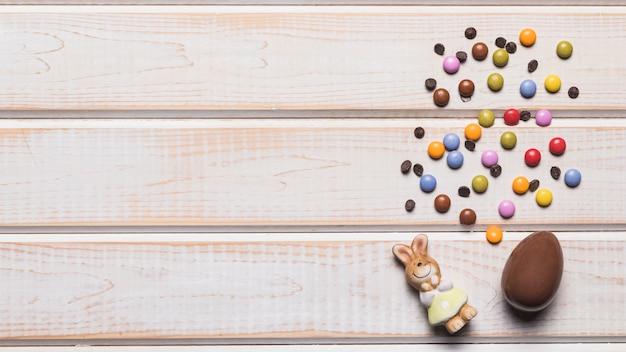 Konijn beeldje; paasei; gem-snoepjes met chocoladeschilfers op houten bureau Gratis Foto