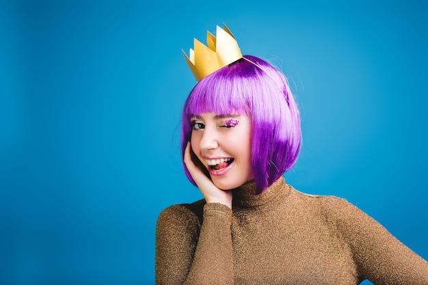 Koninklijk portret van vrolijke jonge vrouw in luxekleding, gouden kroon die pret heeft. tong tonen, geluk, speelse opgewekte stemming, geweldig feest, paars haar knippen. Gratis Foto