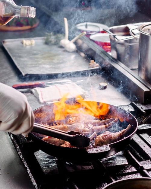 Kook het vlees van braadribben gezouten binnen zwarte metaalpan in de keuken Gratis Foto