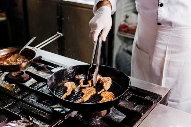 Kook het voorbereiden van vleesribben binnen zwart metaalpan in de keuken Gratis Foto