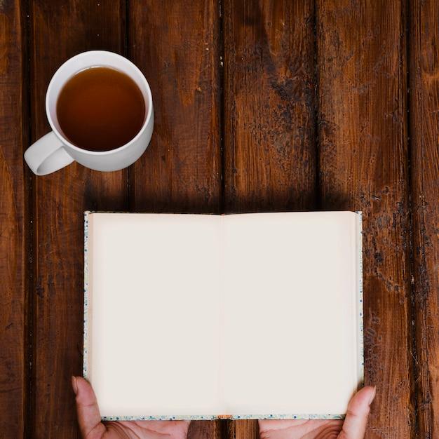 Kop aromatische thee en open boek op oud hout Gratis Foto