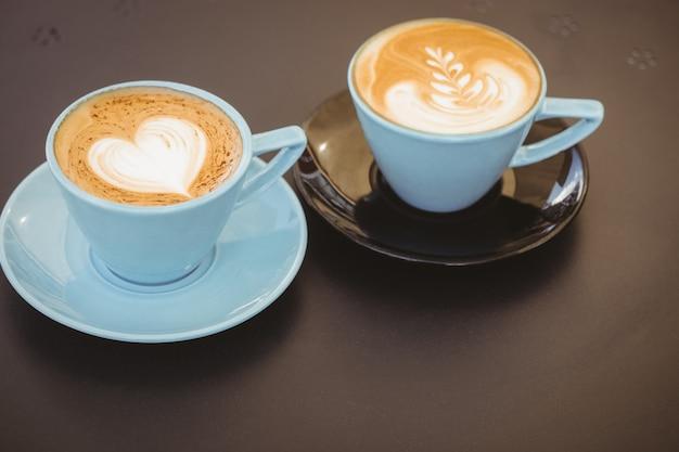 Kop cappuccino met koffiekunst op houten lijst bij koffiewinkel Premium Foto
