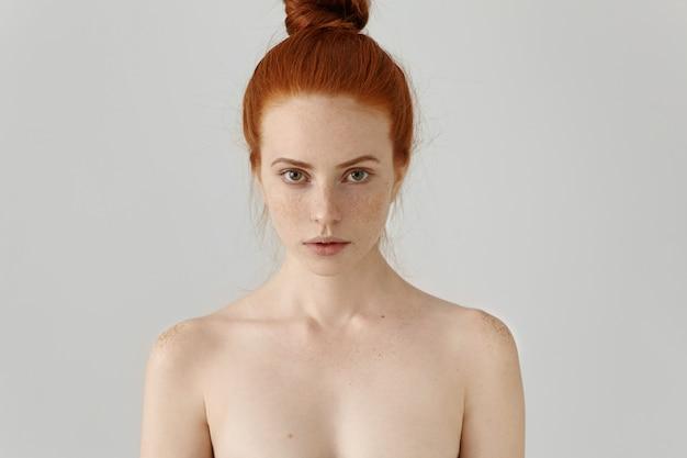Kop en schouders van aantrekkelijke jonge vrouwelijke model met gember haar broodje en sproeten topless poseren op blinde muur. schoonheid en huidverzorging concept. Gratis Foto