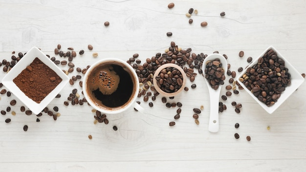 Kop koffie; koffie poeder en koffiebonen gerangschikt in een rij op het bureau Gratis Foto