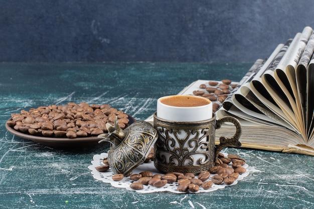 Kop schuimende koffie, plaat van koffiebonen en boek over marmeren lijst. Gratis Foto