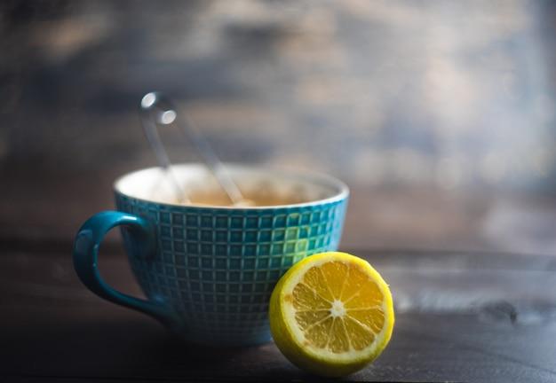 Kop thee met citroen en kruiden op donkere houten achtergrond met exemplaarruimte Premium Foto