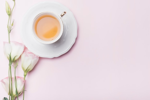 Kop thee met eustomabloemen op roze achtergrond Gratis Foto
