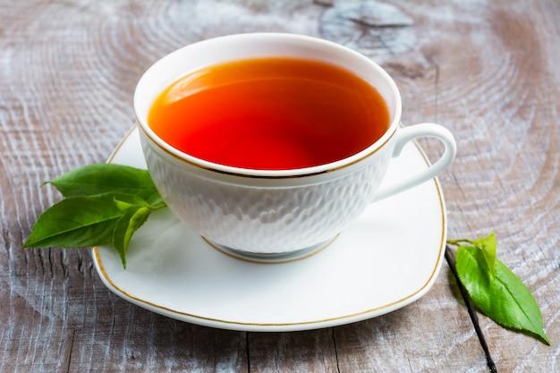 Kop thee met groene bladeren op rustieke houten lijst Premium Foto