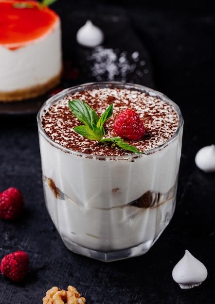 Kop tiramisu met cacaopoeder en framboos met munt. Gratis Foto