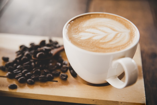 Kop van koffie latte op houten lijst in de koffie van de koffiewinkel Gratis Foto