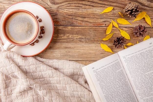 Kop warme koffie met geopend boek op houten achtergrond. herfst concept Premium Foto