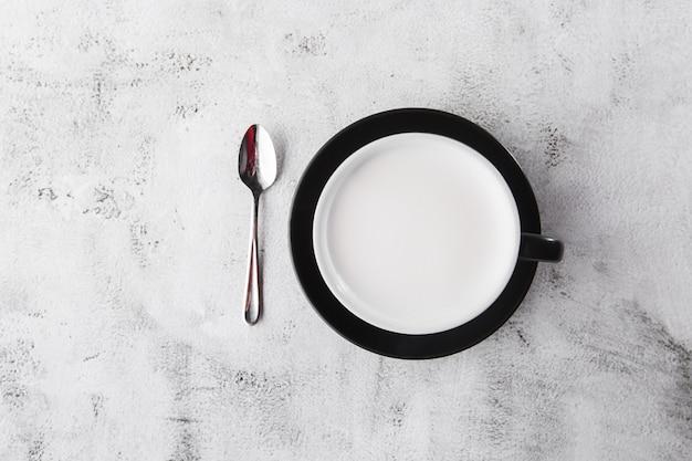 Kop warme melk in donkere kop geïsoleerd op lichte marmeren achtergrond. bovenaanzicht, kopieer ruimte. reclame voor café-menu. coffeeshop menu. horizontale foto. traditionele drankjes voor de winter Premium Foto