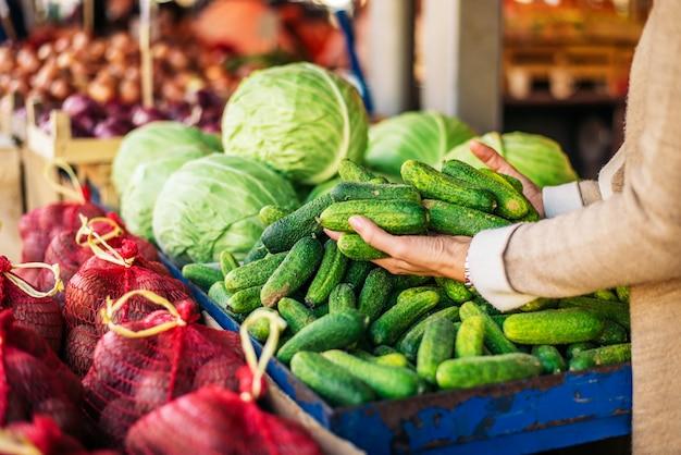Kopen van verse komkommers op boerenmarkt. onherkenbaar persoon. Premium Foto