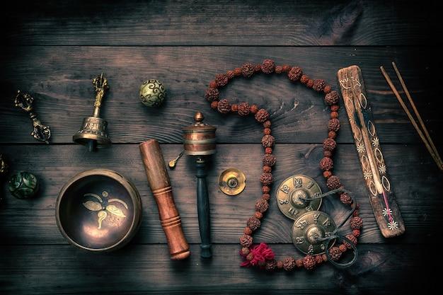 Koperen klankschaal, gebedskralen, gebedtrommel en andere tibetaanse religieuze voorwerpen voor meditatie Premium Foto