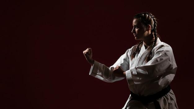 Kopieer de ruimte rode achtergrond en vrouw in witte karate uniform Gratis Foto