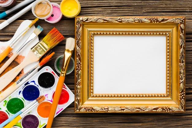 Kopieer ruimte gouden canvas frame en borstels Gratis Foto