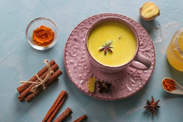 Kopje ayurvedische gouden kurkuma latte melk met kurkumapoeder, kaneel, gember en anijs ster op lichtblauw oppervlak, bovenaanzicht Premium Foto