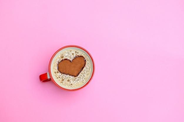 Kopje cappuccino koffie met hartvorm op zachte roze achtergrond. goedemorgen concept. afbeelding met kopie ruimte, bovenaanzicht Premium Foto