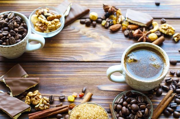 Kopje espresso zwarte koffie op natuurlijke houten met gezonde snacks noten en rozijnen. copyspace in het midden. Premium Foto