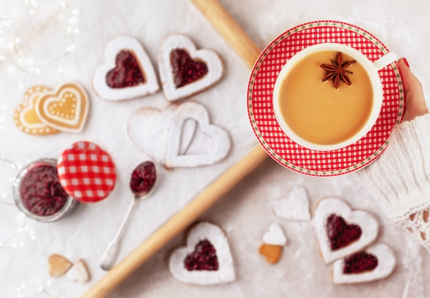 Kopje gearomatiseerde thee chai gemaakt door zwarte thee te zetten met aromatische kruiden en kruiden met zelfgemaakte hartvormige koekjes met frambozenjam Premium Foto