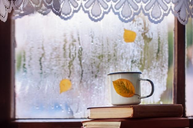 Kopje herfst thee of koffie en gele bladeren op regenachtige venster Premium Foto