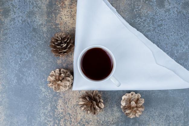 Kopje hete thee en dennenappels op marmeren tafel. hoge kwaliteit foto Gratis Foto