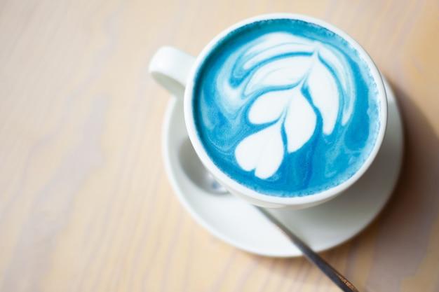 Kopje hete vlinder erwt latte of blauwe spirulina latte op houten tafel Premium Foto