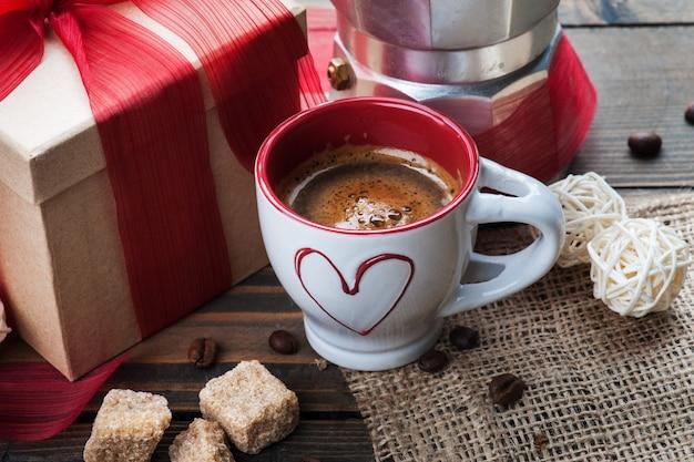 Kopje koffie, cadeau met rood lint, bruine suiker Premium Foto