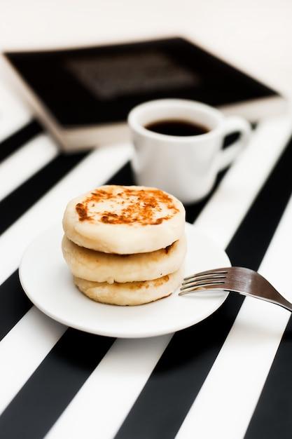 Kopje koffie en bakkerij op gestreepte zwart-witte achtergrond. Premium Foto