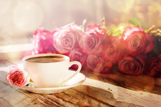 Kopje koffie en boeket roze rozen op tafel Premium Foto