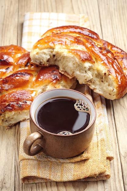 Kopje koffie en zoet broodje op een houten tafel Premium Foto