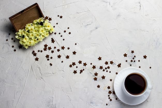 Kopje koffie, houten vintage doos met bloemen en veel kleine sterren op een lichte stenen achtergrond Premium Foto