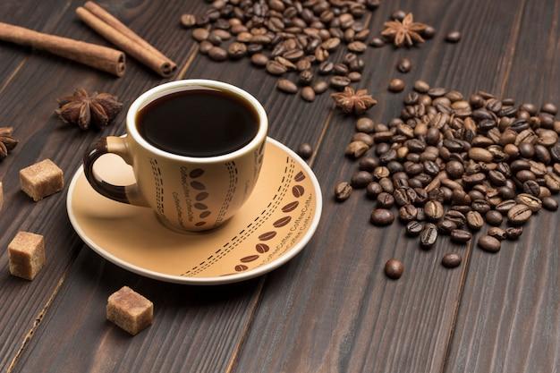 Kopje koffie, koffiebonen gestrooid op tafel. kruiden steranijs en stukjes bruine suiker. Premium Foto