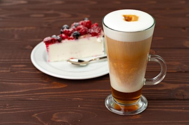 Kopje koffie latte met stuk bessen cheesecake close-up Premium Foto