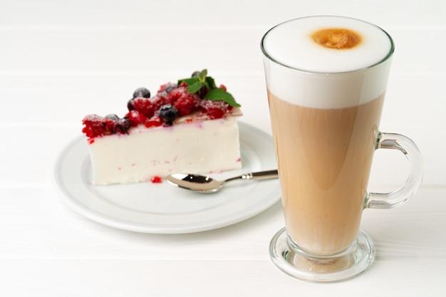 Kopje koffie latte met stuk bessenkaastaart Premium Foto